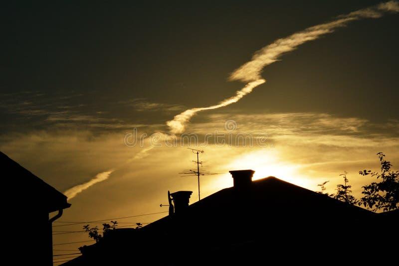Molnig solnedgång i by royaltyfria bilder