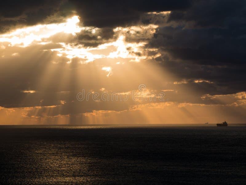 Molnig solnedgång med strålar över havet royaltyfri fotografi