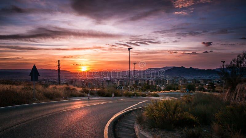 Molnig solnedgång nära vägen till Granada i Spanien arkivbilder