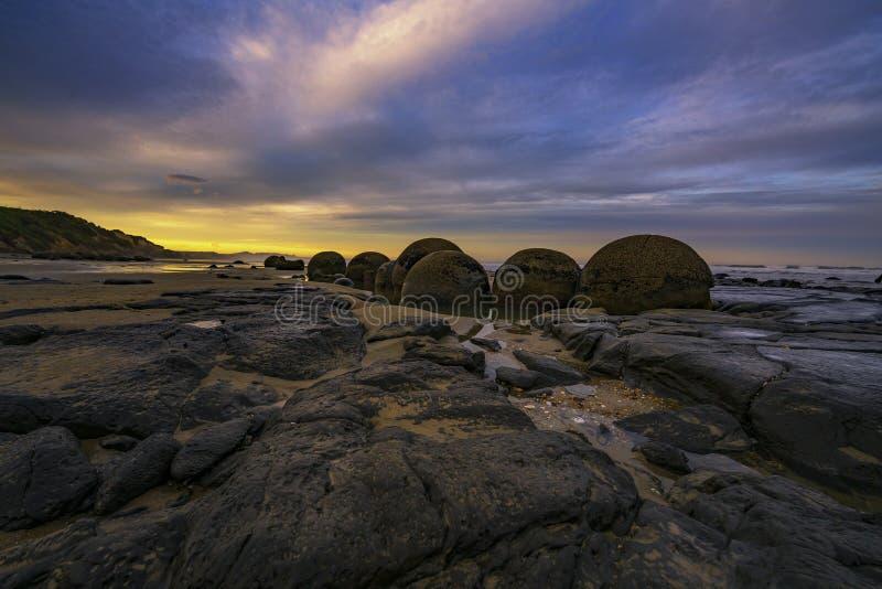 Molnig solnedgång på Moeraki stenblock över den Otago kustlinjen, södra ö, Nya Zeeland fotografering för bildbyråer
