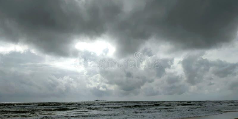 Molnig strand p? solnedg?ngen arkivfoton