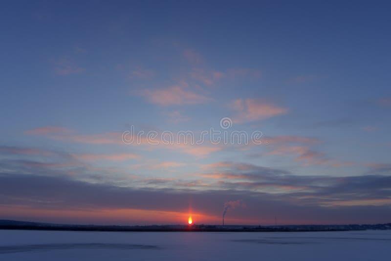 Molnig vintersolnedgång över den iskalla floden royaltyfri bild