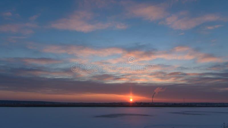 Molnig vintersolnedgång över den iskalla floden i blått och apelsinen, selektiv fokus royaltyfria foton