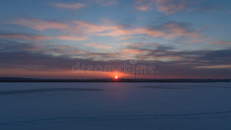 Molnig vintersolnedgång över den iskalla floden i blått och apelsinen, selektiv fokus royaltyfri foto
