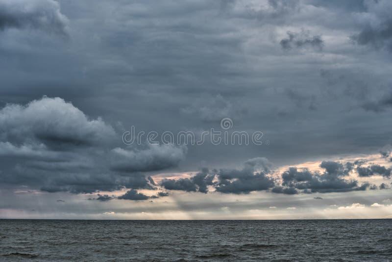 Molniga och stormiga moln ovanför Östersjön i Lettland baltiska estonia nära havssomethere tallinn Aftonfotofors royaltyfri bild