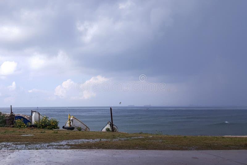 Molnigt väder på kusten, surfare rider i regnet som hänger fördunklar royaltyfri bild