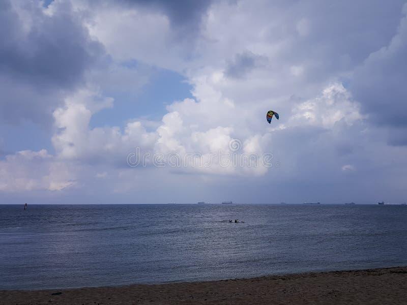 Molnigt väder på kusten, surfare rider i regnet som hänger fördunklar arkivbild