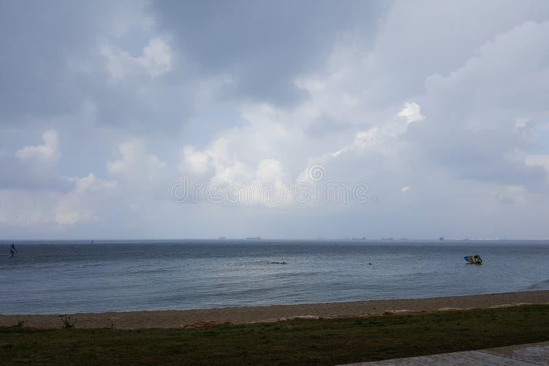 Molnigt väder på kusten, surfare rider i regnet som hänger fördunklar royaltyfri fotografi