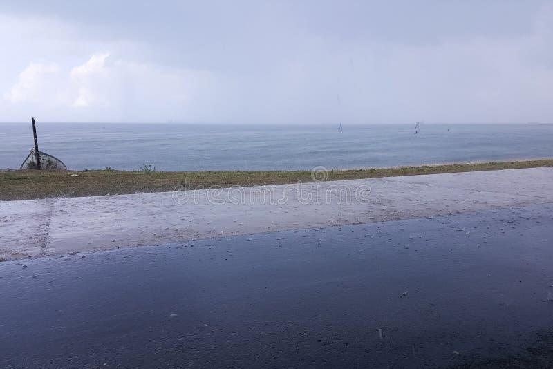 Molnigt väder på kusten, surfare rider i regnet som hänger fördunklar arkivbilder
