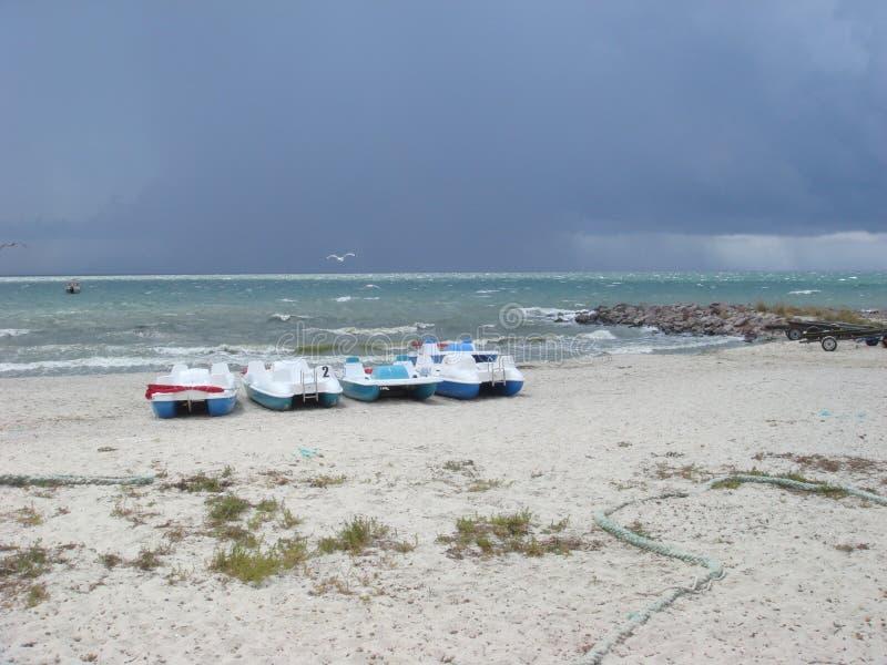 molnigt ?ver havsskyen Stormmoln som bildar över det klara havet Katamaran på en sandig strand arkivbild