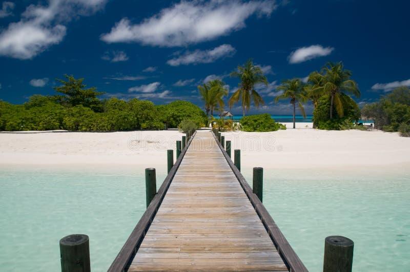 Molo che piombo ad un'isola tropicale immagini stock libere da diritti