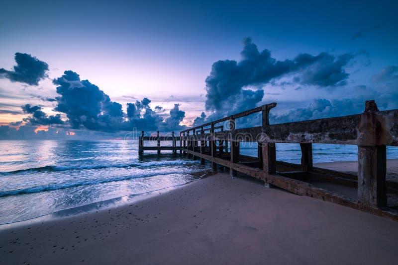 Molo concreto lungo il lato al mare fotografia stock