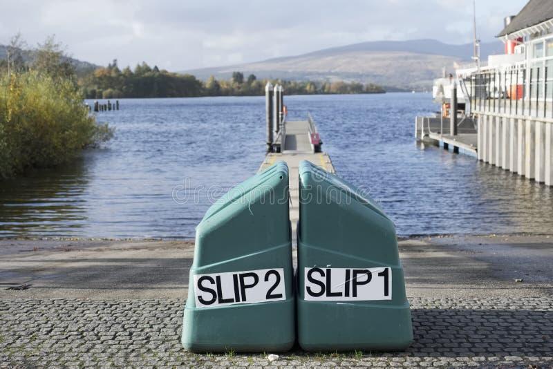 Molo dello scalo di alaggio al lancio del lago del lago per i crogioli e le canoe di acqua a Lomond Scozia immagini stock libere da diritti