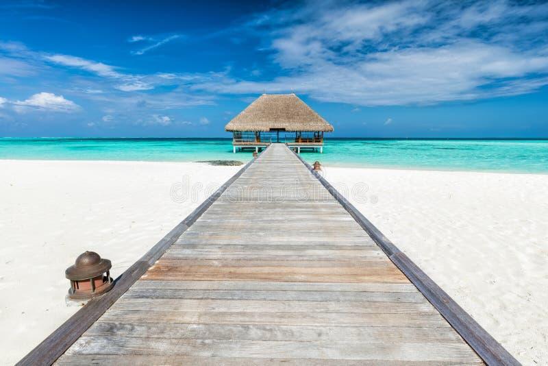 Molo di legno che conduce alla casetta di rilassamento Isole dei Maldives fotografie stock libere da diritti