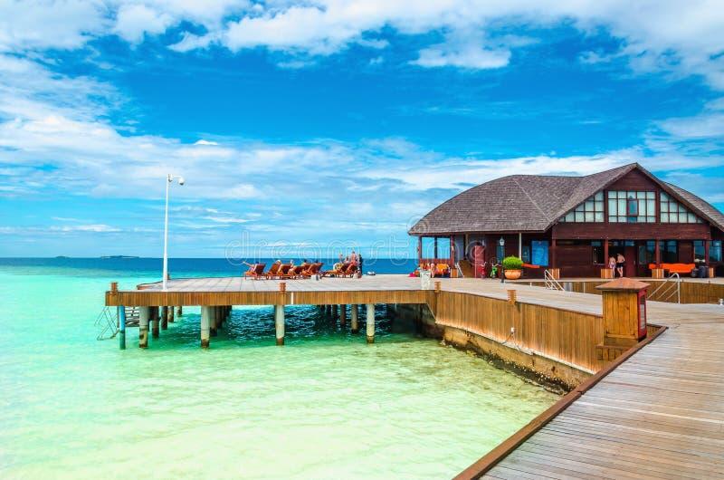 Molo di legno con il bungalow di nad di sedie a sdraio sui precedenti dell'acqua azzurrata dell'Oceano Indiano immagine stock