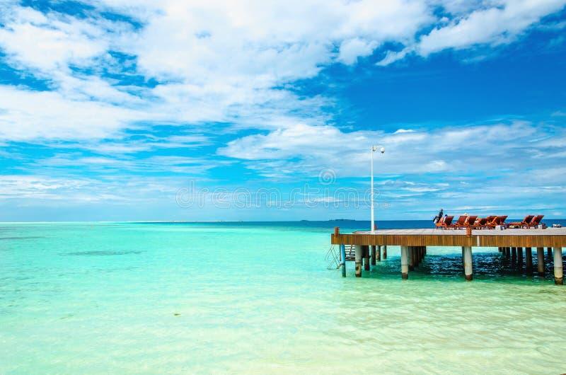 Molo di legno con le sedie a sdraio sui precedenti dell'acqua azzurrata dell'Oceano Indiano fotografia stock libera da diritti