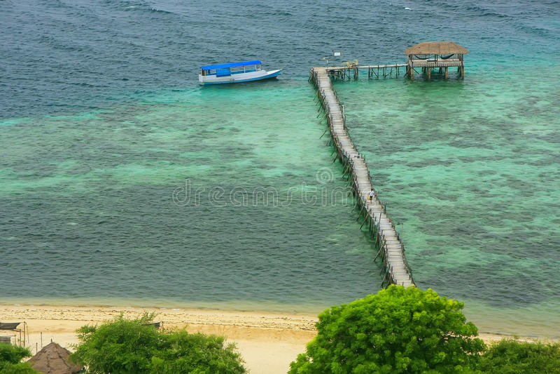 Molo di legno lungo all'isola di Kanawa nel mare del Flores, Nusa Tenggara, fotografia stock libera da diritti