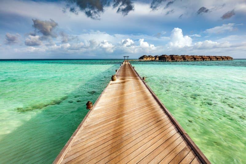 Molo di legno sull'oceano sulle isole delle Maldive immagini stock