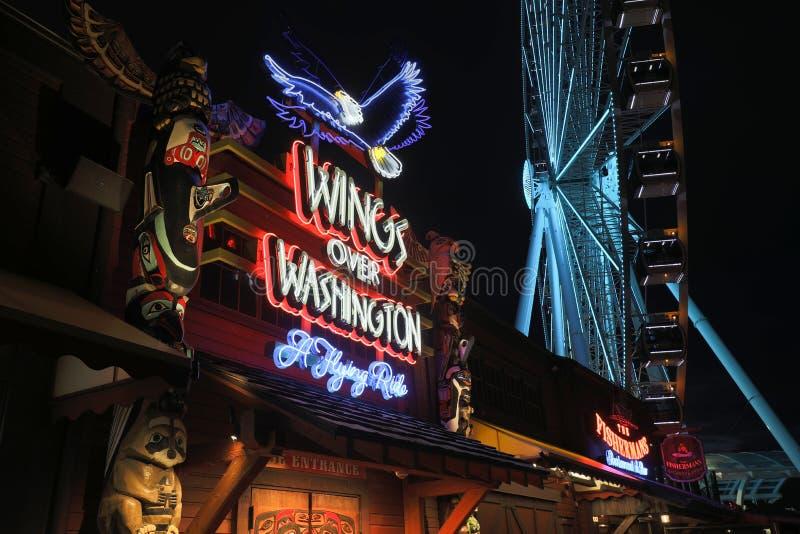 Molo 57 przy nocą z neonowymi znakami turystyczni biznesy Wielki Ferris i Toczy wewnątrz Seattle zdjęcia stock