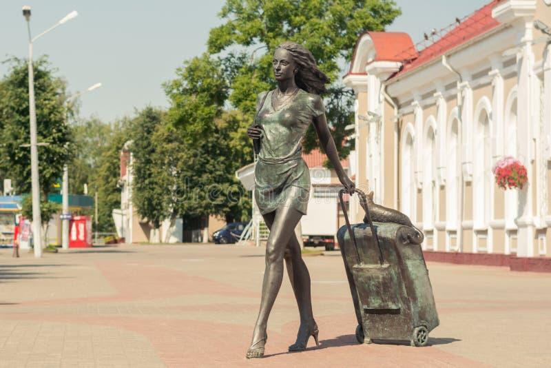 Molodechno, Vitryssland 07 21 2019 Skulptur 'En passagerare med resväska på hjul På resväskan ligger katten, järnvägsstaten royaltyfri foto