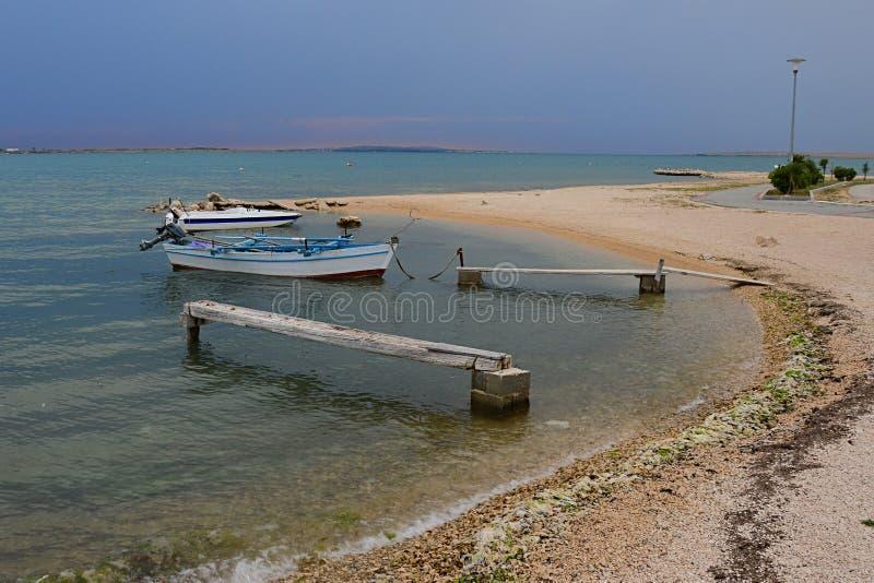 Molos di legno vacillante e barche del pescatore sulla spiaggia in Croazia durante il giorno nuvoloso prima della pioggia immagine stock libera da diritti