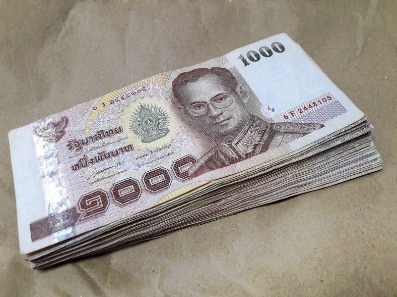 Molta banconota della Tailandia da 1.000 baht disposta su carta marrone immagini stock libere da diritti