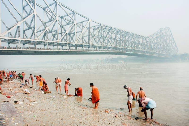Molta gente che bagna nel fiume Hooghly sotto il bus immagini stock