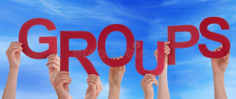 Molta gente passa la tenuta dei gruppi di parole rossi cielo blu fotografie stock libere da diritti