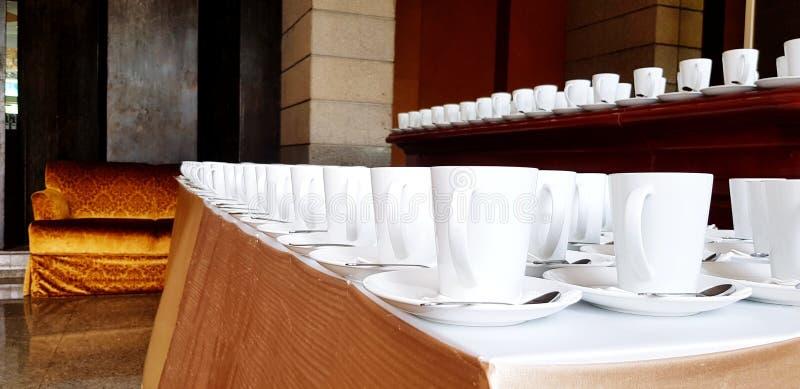 Molta tazza di caffè o tè e cucchiaio di acciaio inossidabile che mette sulla tavola bianca per il cliente servente fotografie stock libere da diritti