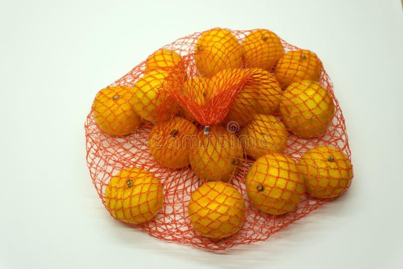 Molte arance imballate in reticolato per essere vendita in una stalla di frutti fotografia stock libera da diritti