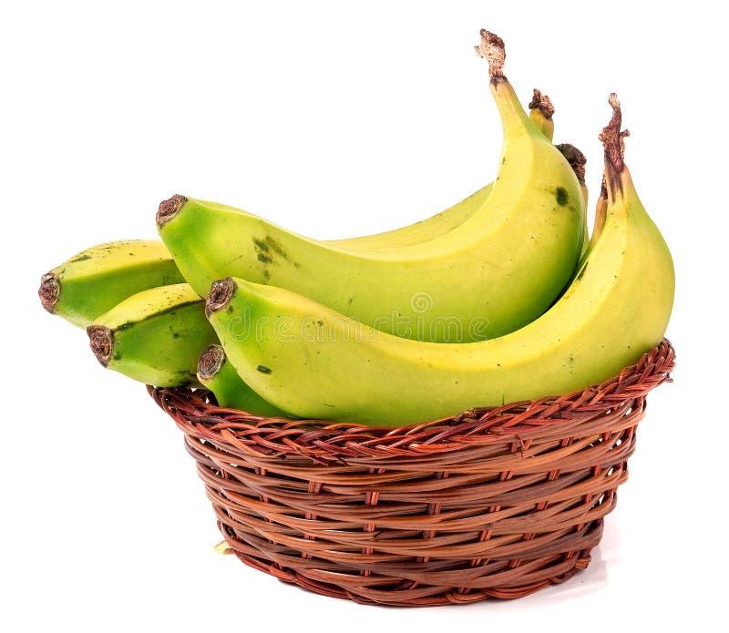 Molte banane verdi in canestro di vimini marrone isolato su bianco immagine stock libera da diritti