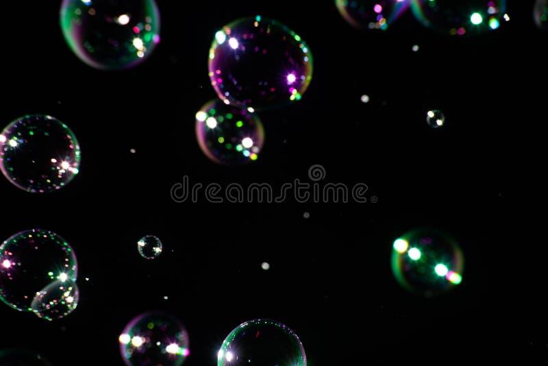 Molte bolle di sapone su un fondo scuro, fuoco molle fotografie stock