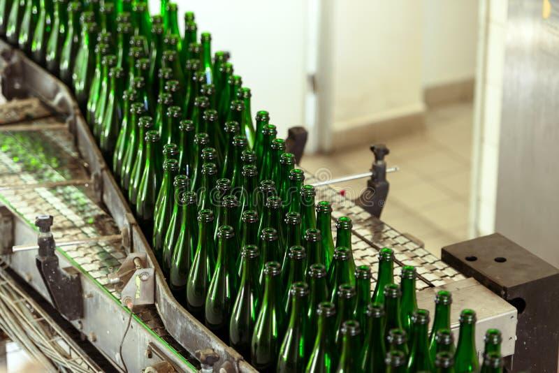 Molte bottiglie sul nastro trasportatore fotografia stock libera da diritti