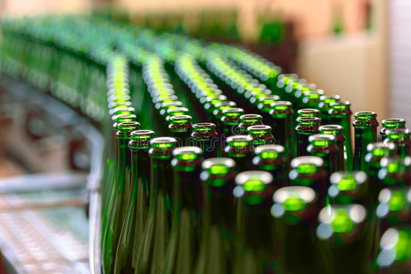 Molte bottiglie sul nastro trasportatore fotografia stock