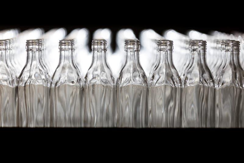 Molte bottiglie sul nastro trasportatore in fabbrica di vetro fotografia stock