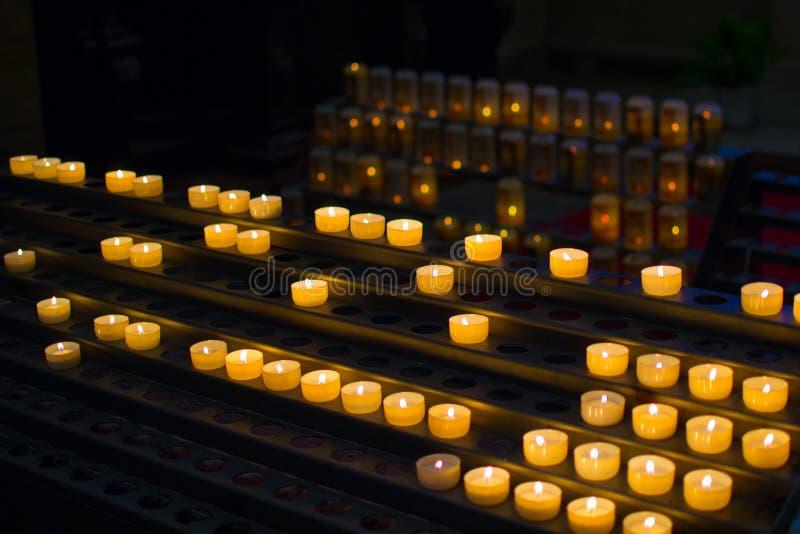 Molte candele brucianti in una fila con profondità di campo bassa immagini stock