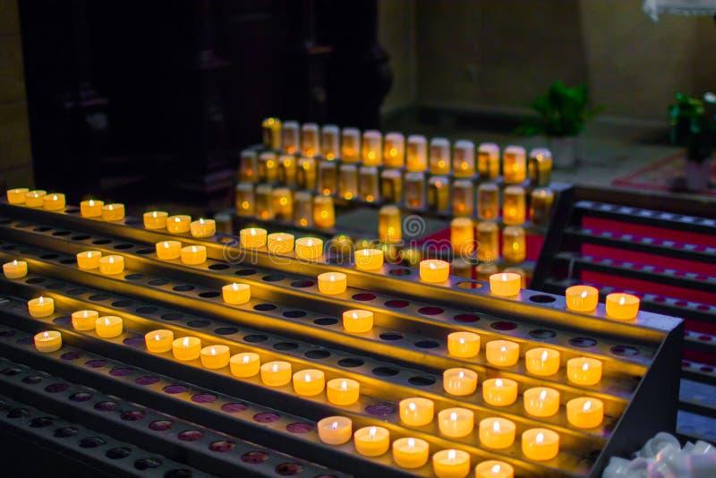 Molte candele brucianti in una fila con profondit? di campo bassa immagine stock
