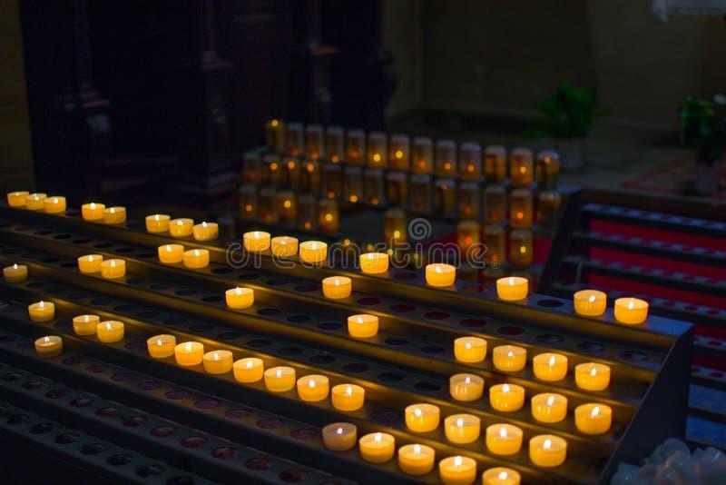 Molte candele brucianti in una fila con profondit? di campo bassa immagini stock