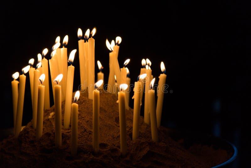 Molte candele danno la luce gialla calda nel fondo nero fotografia stock