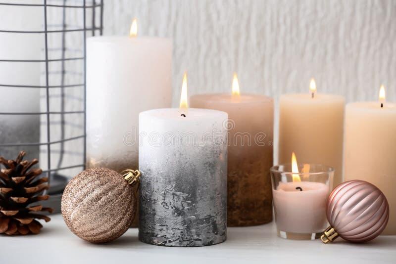 Molte candele e decorazioni brucianti di Natale sulla tavola immagini stock