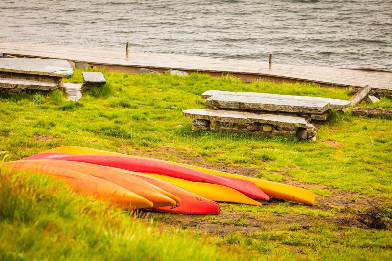 Molte canoe sulla riva norvegese del fiordo fotografie stock