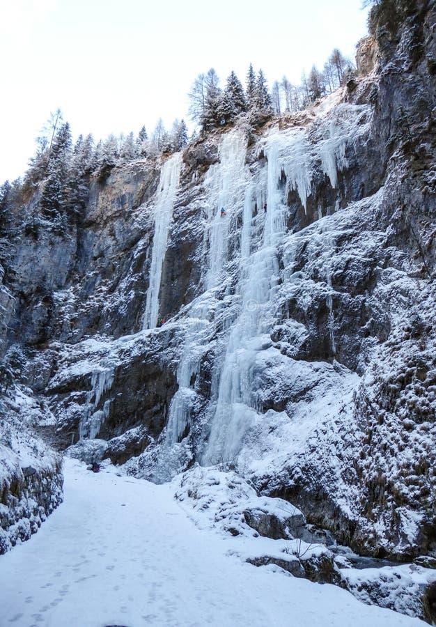 Molte cascate congelate con gli scalatori su ghiaccio estremi su loro un giorno di inverno freddo nelle dolomia in Italia fotografia stock libera da diritti
