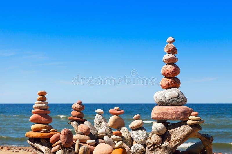 Molte della piramide di zen della roccia dei ciottoli bianchi e rosa su un fondo di cielo blu e del mare immagine stock