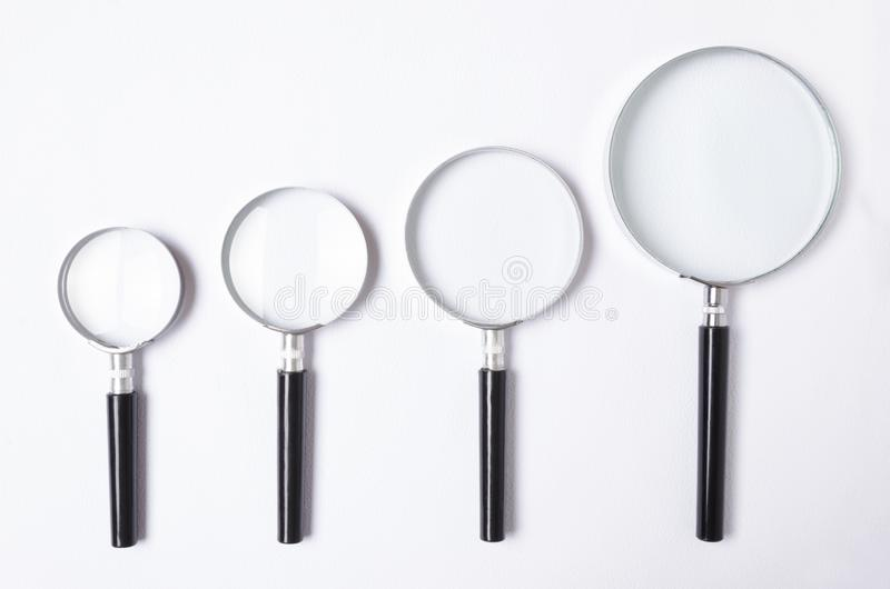 Molte dimensioni della lente d'ingrandimento sulla tavola bianca, vista superiore immagine stock