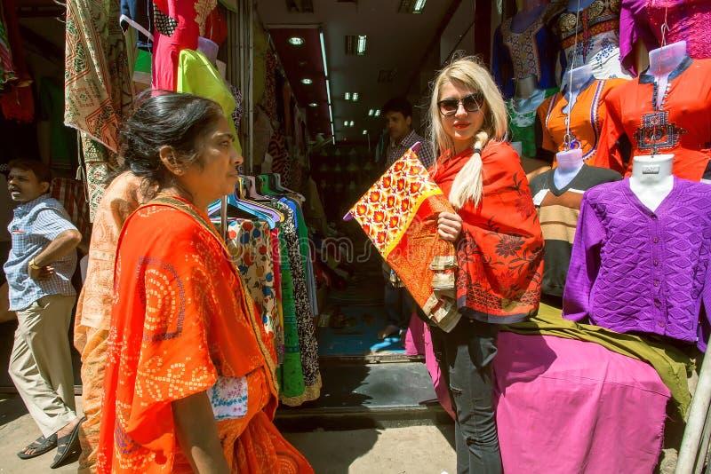Molte donne che vanno a fare spese alla via del mercato con i depositi del tessuto fotografia stock libera da diritti