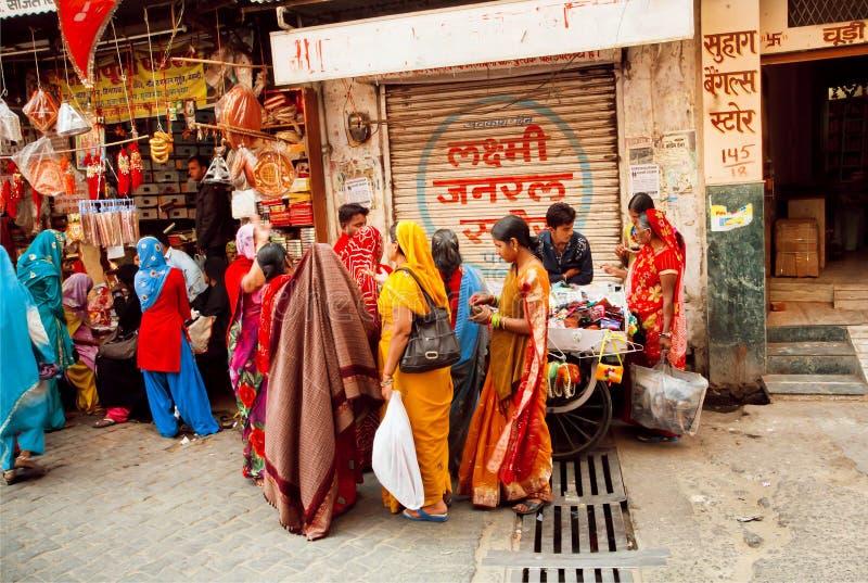 Molte donne vestite variopinte che camminano per comperare fotografia stock libera da diritti