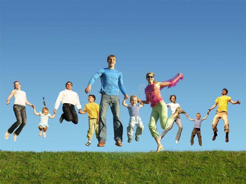 Molte famiglie di salto sull'erba, collage immagini stock