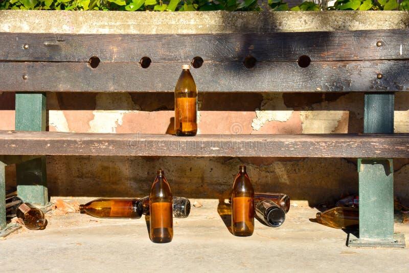 molte grandi bottiglie arancio della birra fatte di vetro completamente vuoto al parco dovuto qualcuno ha bevuto il tempo prima d fotografie stock libere da diritti