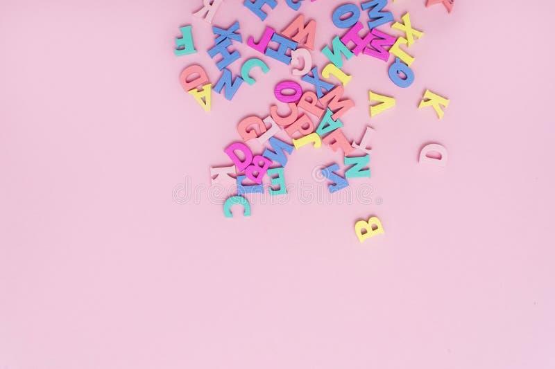 Molte lettere di legno multicolori su un fondo rosa Lettere del giocattolo Alfabeto inglese Vista da sopra Disposizione piana Cop fotografia stock