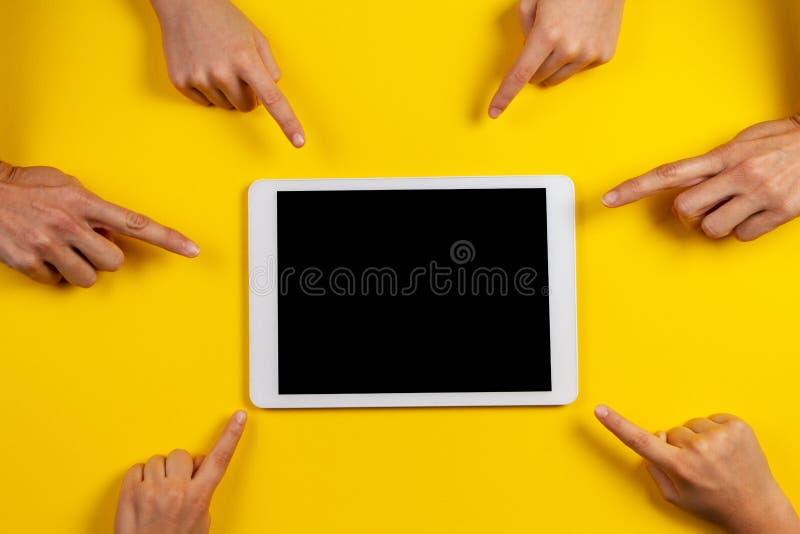 Molte mani che indicano il computer bianco della compressa con lo schermo in bianco su fondo giallo fotografia stock